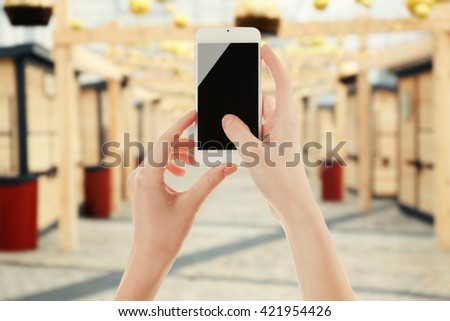 Female hands shows mobile smart phone, blurred background - stock photo