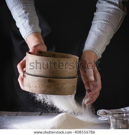Female hands sifting flour from old sieve on old wooden kitchen table. Dark rustic style. Square image - stock photo