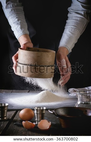 Female hands sifting flour from old sieve on old wooden kitchen table. Vintage kitchenware with flour, water and eggs at foreground. Dark rustic style. - stock photo