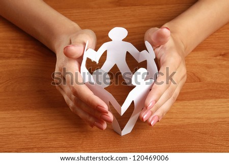 Female hands taking care of paper people, isolated on grey - stock photo