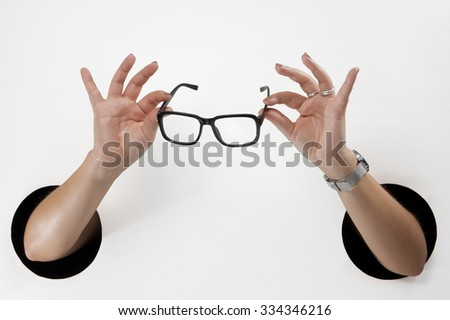 Female  hands through the holes on a white background are holding the black-framed glasses - stock photo