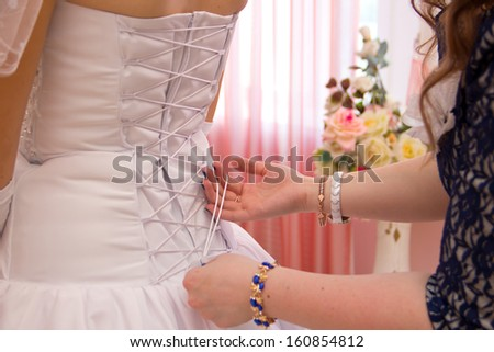 Female hands tightening a corset to the bride - stock photo