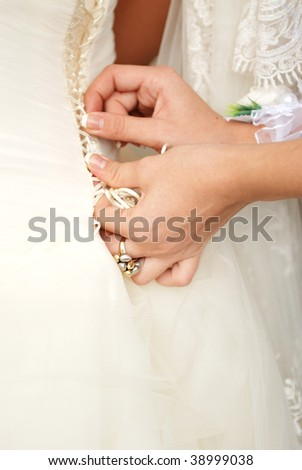 Female hands tightening a corset to the bride.