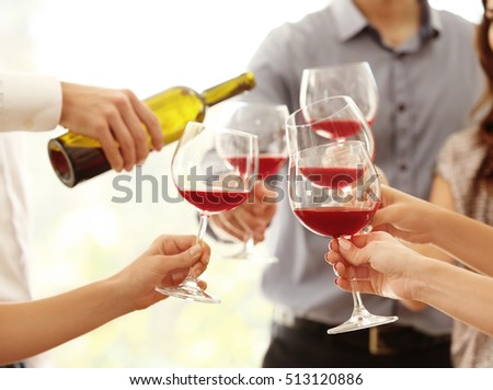 Female hands toasting with glasses of red wine, closeup