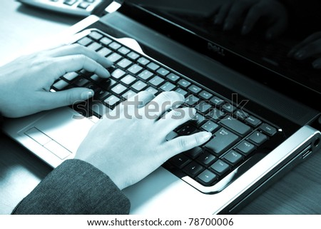 Female hands typing on a laptop - blue toned image - stock photo