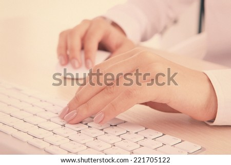 Female hands typing on keyboard on light background - stock photo