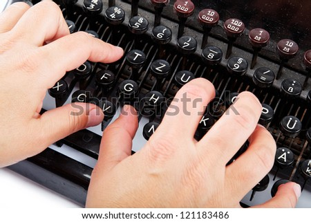 Female hands typing on the keyboard of the old mechanical typewriter. - stock photo