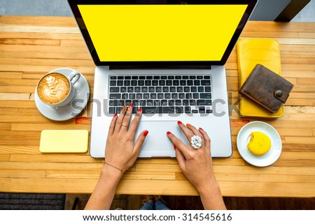 Female hands typing on the laptop with coffee cup, phone, sweet cake and wallet on the wooden table - stock photo