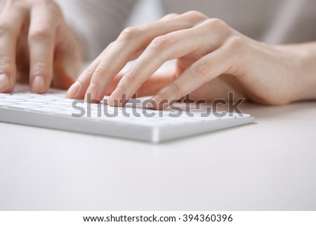 Female hands using keyboard on white wooden table, close up
