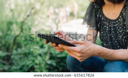 female hands using tablet on nature background close-up . The Internet and social media in nature.