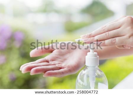 Female hands using wash hand sanitizer gel pump dispenser. - stock photo