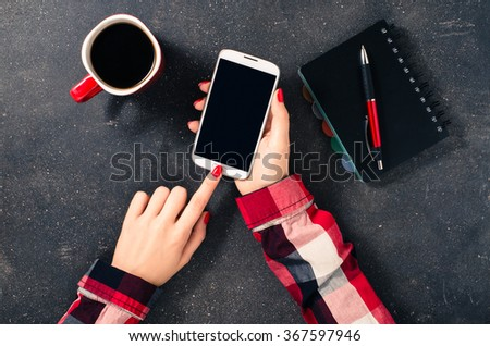 Female hands using white mobile phone over dark table - stock photo