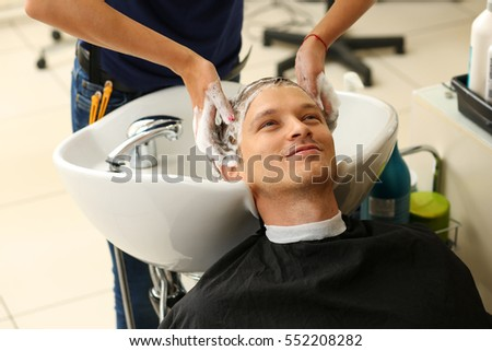 Female hands washing hair handsome smiling stock photo 552208282 female hands washing hair to handsome smiling man at hairdresser with shampoo before haircut keratin winobraniefo Gallery