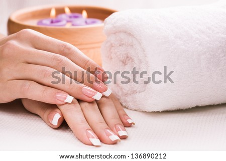 female hands with aromatic candles and towel - stock photo