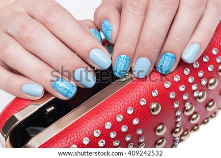 Female hands with blue manicure holding a red handbag - stock photo