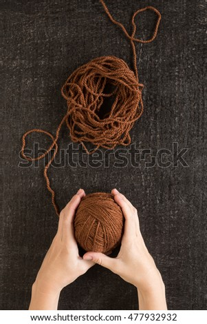 Female hands with brown yarn