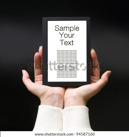 Female hands with electronic book on the dark background - stock photo