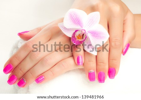 female hands with fragrant orchid and towel - stock photo