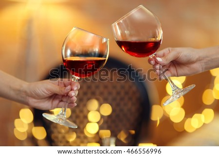 Female hands with glasses of wine on blurred background