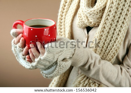 Female hands with hot drink, on color background - stock photo