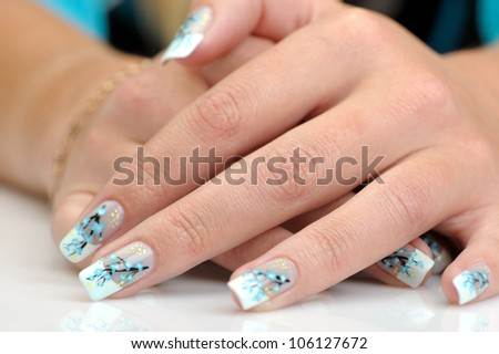 Female hands with manicure close up. Drawing of a branch with blue flowers.With reflection