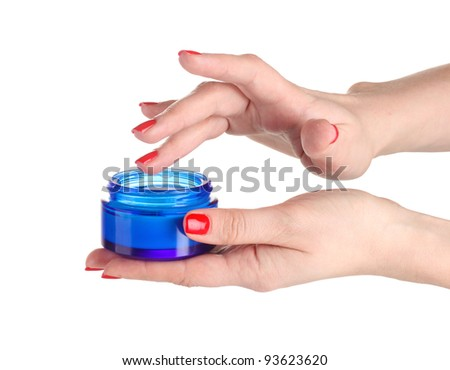 Female hands with manicure holding cream isolated on white - stock photo