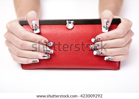 Female hands with manicures in Russian style holding a red handbag. Hands and nails closeup. isolated on white background. - stock photo