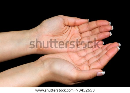 Female hands with open palm over black background