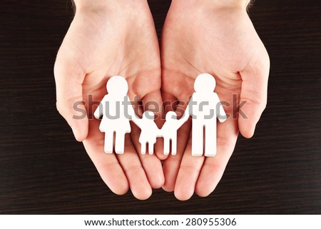 Female hands with paper family on wooden background
