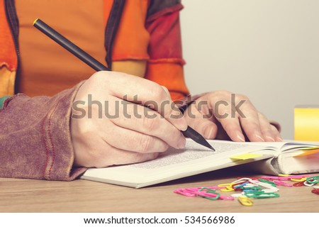 Female hands with pen writing on book. Education concept.
