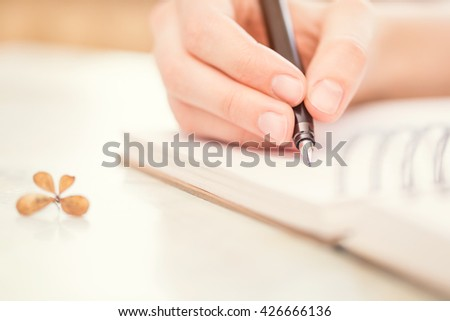 Female hands with pen writing on notebook.