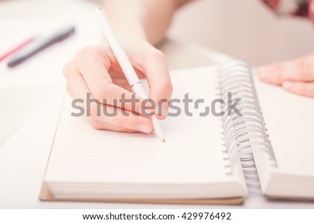 Female hands with pen writing on notebook. - stock photo