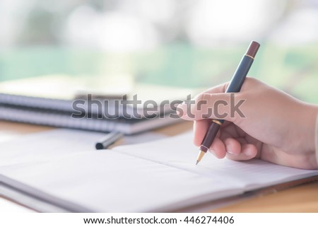 female hands with pen writing on notebook  coffee  cafe