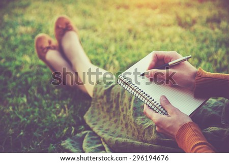 female hands with pen writing on notebook on grass outside - stock photo