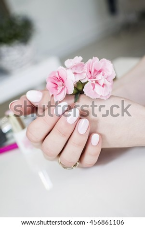 Female hands with pink flower.