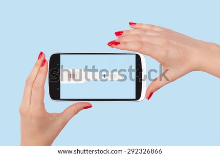 Female hands with red nails holding smartphone with positive pregnancy test isolated on light blue background. The future of medicine. - stock photo
