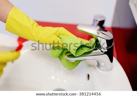 Female hands with rubber protective gloves cleaning tap with green cloth. Spring cleaning - stock photo