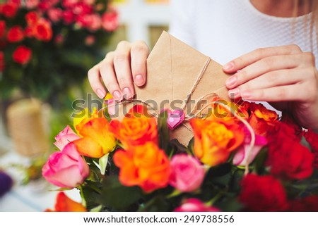 Female hands with small envelope putting it in bouquet of roses