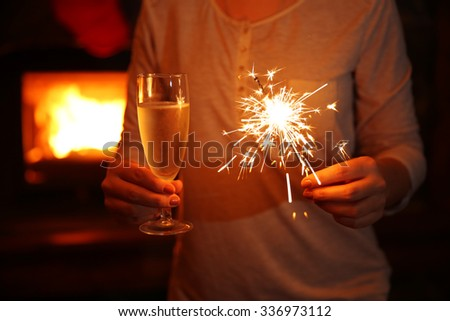 Female hands with sparkler and glass of sparkle wine on fireplace background - stock photo