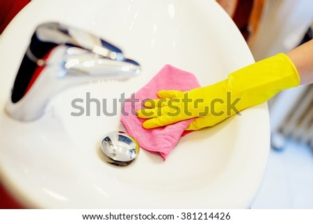 Female hands with yellow rubber protective gloves cleaning sink with pink cloth. Spring cleaning - stock photo