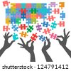 Female hands work together to connect jigsaw puzzle pieces - stock photo