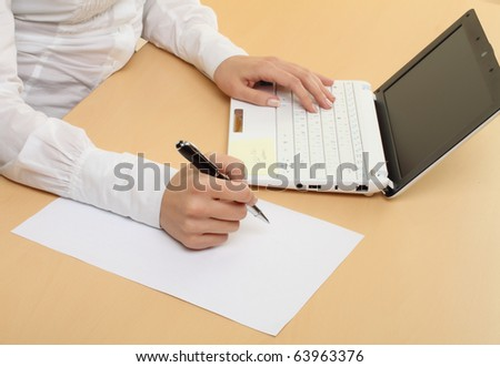 Female hands. working on laptop and spelling on paper. - stock photo