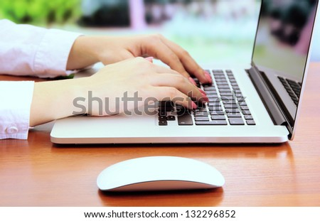 Female hands working on laptop, on bright background