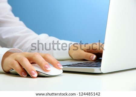female hands writing on laptot, on blue background - stock photo