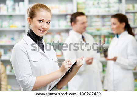 Female happy pharmacist chemist woman standing in pharmacy drugstorewit her colleagues - stock photo