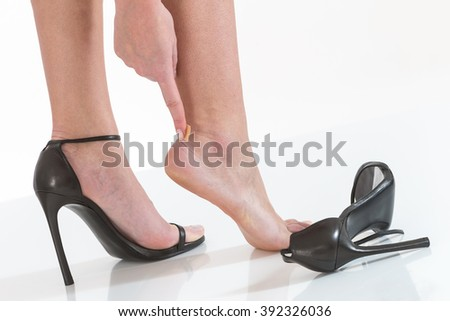 female having pain after wearing high heeled shoes - stock photo