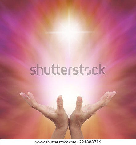Female healing hands outstretched with bright shaft of light and cross above on a golden magenta energy background - stock photo