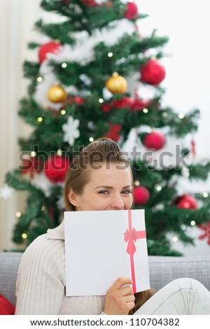 Female hiding behind Christmas postcard - stock photo