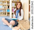 Female high school student at library sitting on the floor - stock photo