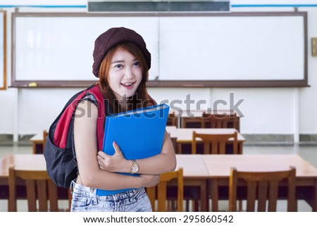 Female high school student carrying backpack and folder smiling on the camera in the classroom